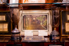 An enlargement of the original postcard that the restoration used as it's guide is flanked by two trophies found in the building.